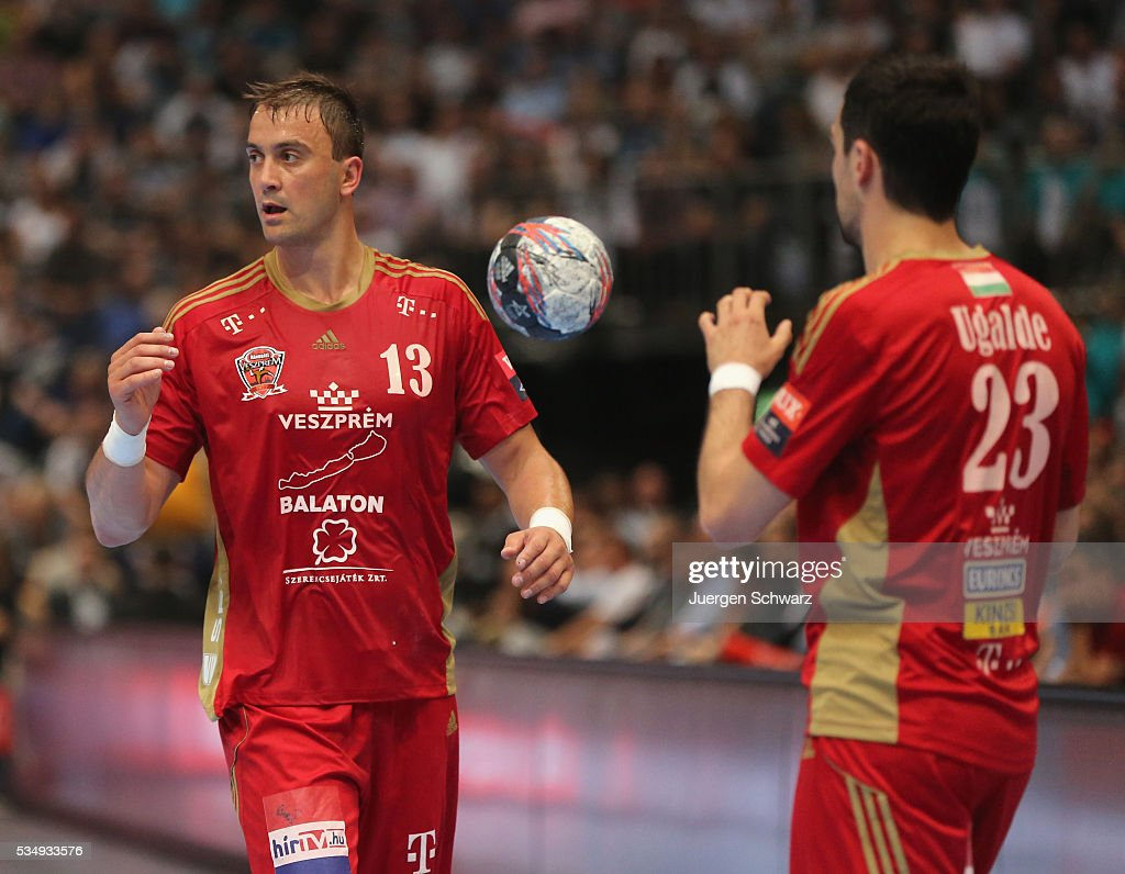 Momir Ilic of Veszprem (L) throws the ball to Cristian Garcia Ugalde during the second semi-final of the EHF Final4 between THW Kiel and MVM Veszprem on May 28, 2016 in Cologne, Germany.