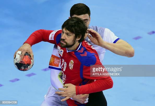 Momir Rnic of Serbia is pushed Ludovic Fabregas of France during the Men's 2016 EHF European Handball Championships match between Serbia and France...
