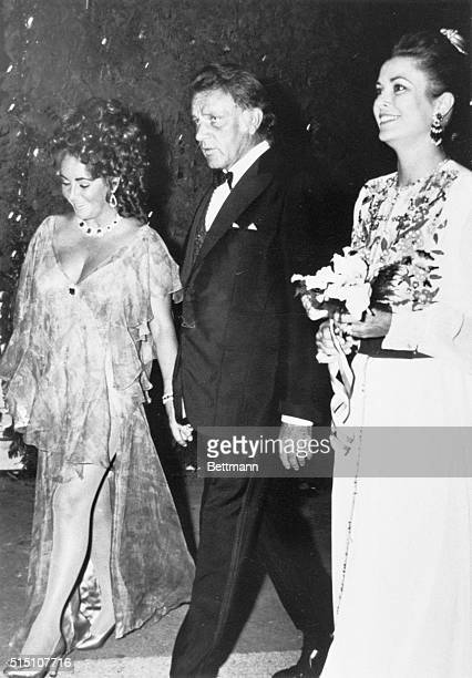 Printed chiffon dress for actress Elizabeth Taylor escorted by her actor husband Richard Burton as both are greeted by Princess Grace of Monaco as...
