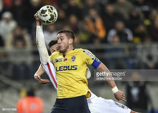 Monaco's Argentinian forward Guido Carrillo tries to kick the ball with his hand despite FC Sochaux' French defender Pierre Gibaud during the French...