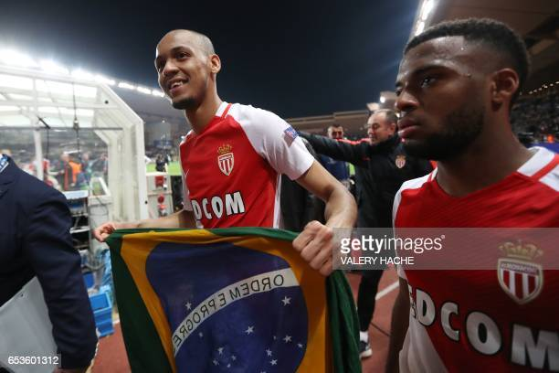Monaco's Brazilian defender Fabinho celebrates with a Brazilian flag at the end of the UEFA Champions League round of 16 football match between...