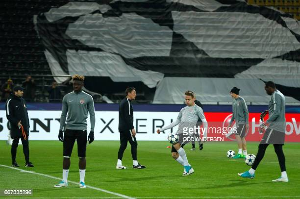 Monaco's French defender Kevin Ndoram Monaco's Portuguese coach Leonardo Jardim and teammates warm up after the game was postponed due to the...