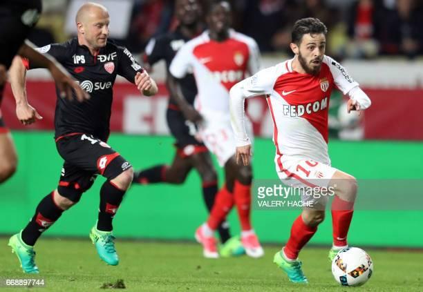 Monaco's Portuguese midfielder Bernardo Silva runs with the ball as Dijon's French midfielder Florent Balmont follows him during the French L1...