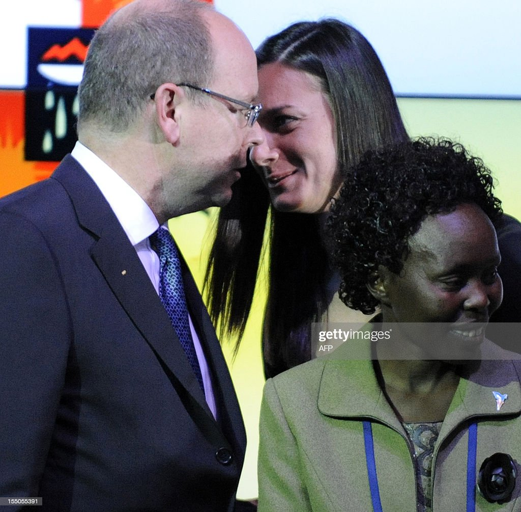 Monaco's Prince Albert II (L) speaks with Russian Olympic champion Yelena Isinbayeva (C) at the Peace and Sport forum in Krasnya Polyana outside Sochi on October 31, 2012. The 2014 Winter Olympic Games will be the biggest international event hosted by Russia since the collapse of the Soviet Union. Woman at right is unidentified.