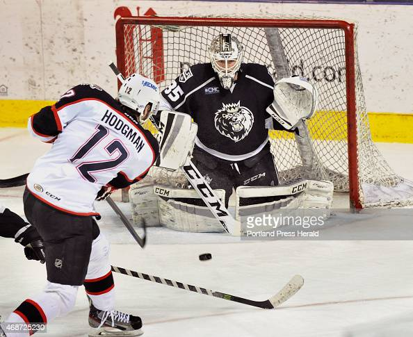 Monarchs goalie JeanFrancois Berube makes a stop as Portland's Justin Hodgman takes the shot as the Portland Pirates host the Manchester Monarchs at...