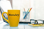 Monday written on yellow coffee or tea cup at wooden boards table, workplace, office sunlight morning background.