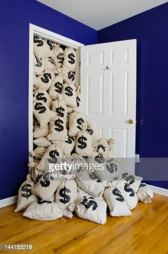 $ money bags flowing out of closet : Stock Photo