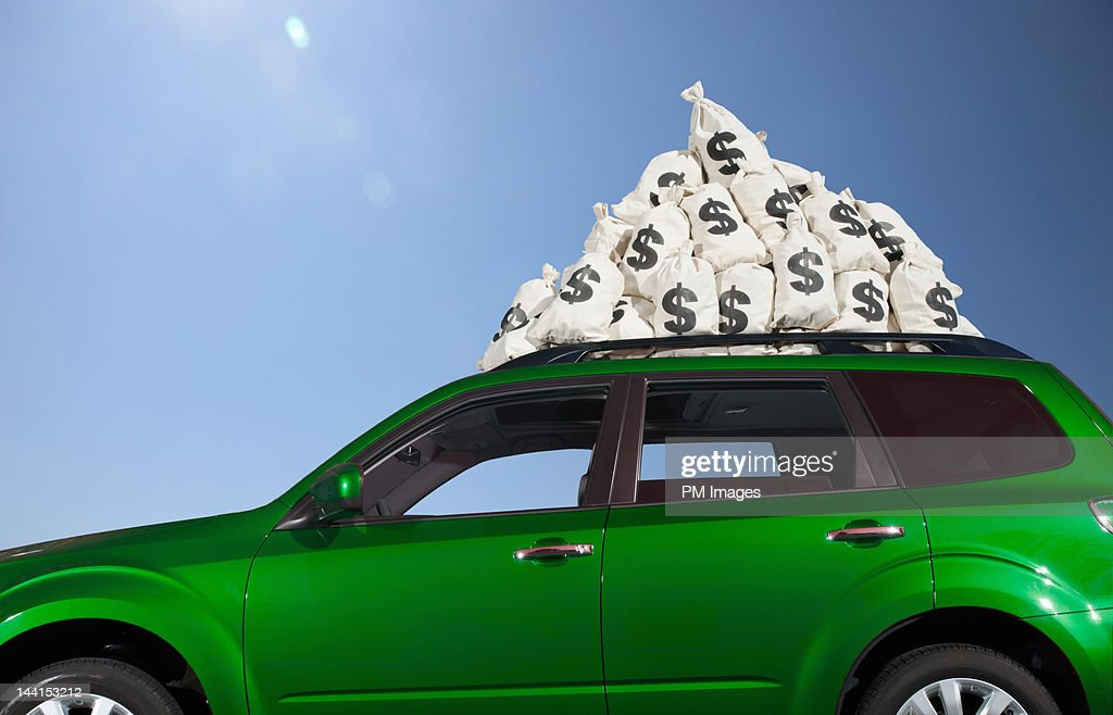 $ money bags piled on car roof : Stock Photo