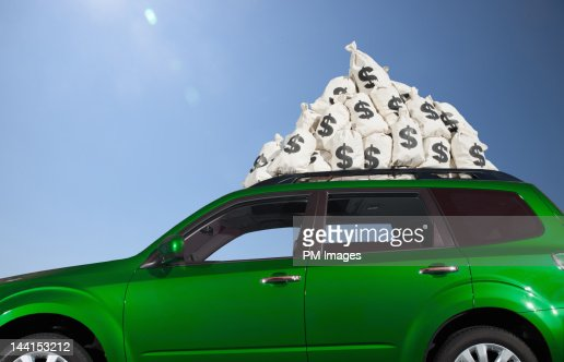 $ money bags piled on car roof : Foto stock