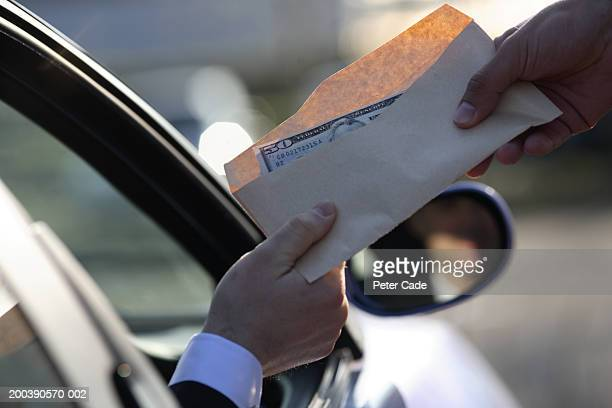 Money being handed over from car, close-up