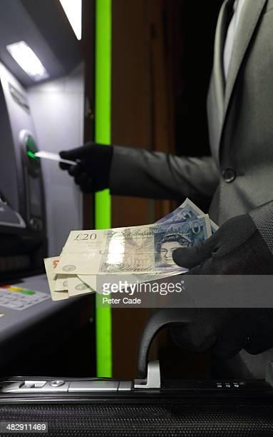 Money being taken from cash point, gloved hands