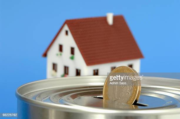 Money box with Euro coin, house in background