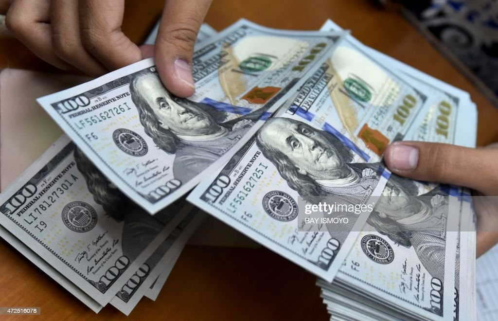A money changer counts US dollar banknotes for customers in Jakarta on May 8, 2015. The dollar rose in Asian trade on fresh expectations the US central bank may raise interest rates in the second half of the year, analysts said. AFP PHOTO / Bay ISMOYO