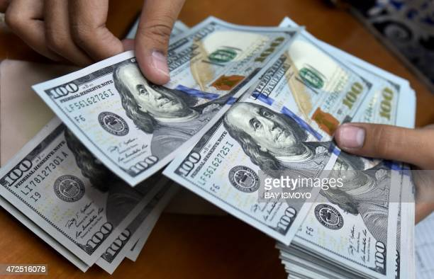 A money changer counts US dollar banknotes for customers in Jakarta on May 8 2015 The dollar rose in Asian trade on fresh expectations the US central...