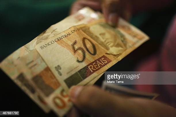 A money changer poses holding reais the Brazilian currency in the Centro neighborhood on March 26 2015 in Rio de Janeiro Brazil Brazil will release...