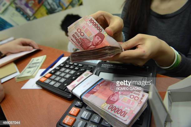 A money changer prepares Indonesian rupiah bills for a customer in Jakarta on March 13 2015 According to reports the rupiah continued its decline...
