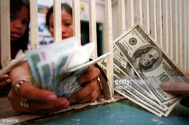 A money changer prepares Philippine peso notes to a customer holding US dollars in Manila 06 September 2000 The Philippine currency plunged to new...