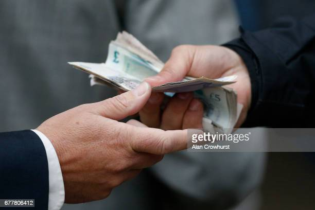 Money changes hands beween punter and bookmaker at Ascot Racecourse on May 3 2017 in Ascot England