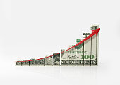 Financial chart textured with one hundred American dollar banknote and a red arrow which is going up on white background. Horizontal composition with copy space. Clipping path is included. Great use f