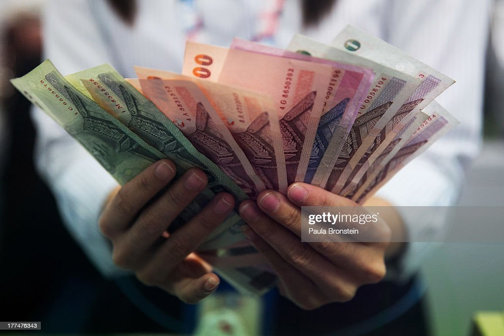 A money exchange bank teller counts Thai bhat before handing it to a customer on August 23, 2013 in Bangkok, Thailand. The local currency dropped to its lowest level since August 2010. Against the US dollar the Thai baht fell to 32.09/32.13 dropping about 5% this year.