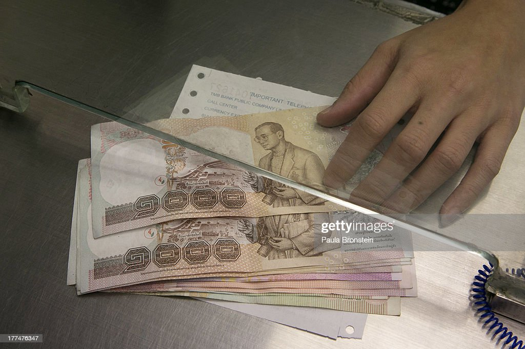 A money exchange bank teller hands over Thai bhat to a customer on August 23, 2013 in Bangkok, Thailand. The local currency dropped to its lowest level since August 2010. Against the US dollar the Thai baht fell to 32.09/32.13 dropping about 5% this year.