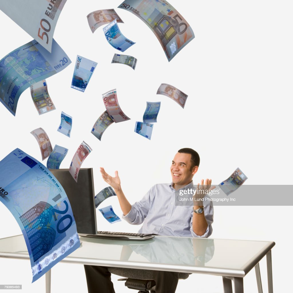 Money flying out of Asian man's computer : Stock Photo