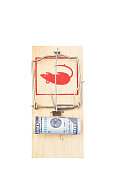 Roll of one hundred dollars in a mousetrap isolated on white background