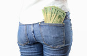 A bunch of cash on a woman's jeans back pocket