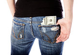 A close-up of a woman's back pocket holding several hundred dollar bills.