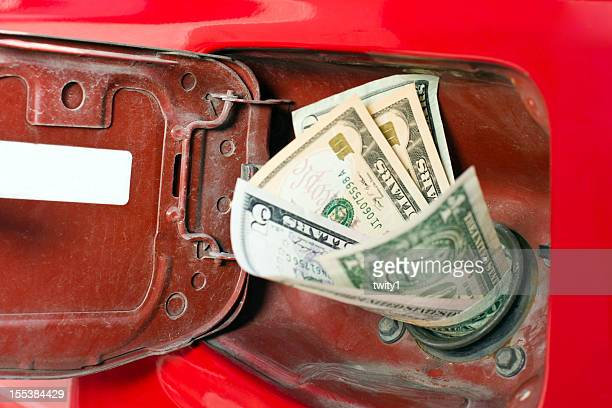 Money in the chute of a gas representing high gas prices