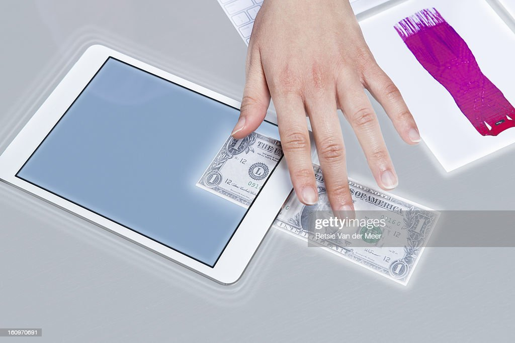 Money is moved from interactive table to i pad. : Stock Photo