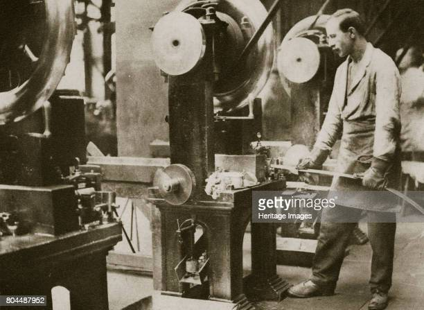 Money making cutting strips of silver into disks 20th century The cutting machine stamps out a double row of disks