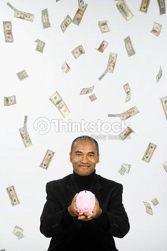 Money Raining Down On Asian Businessman Holding Piggy Bank Stock