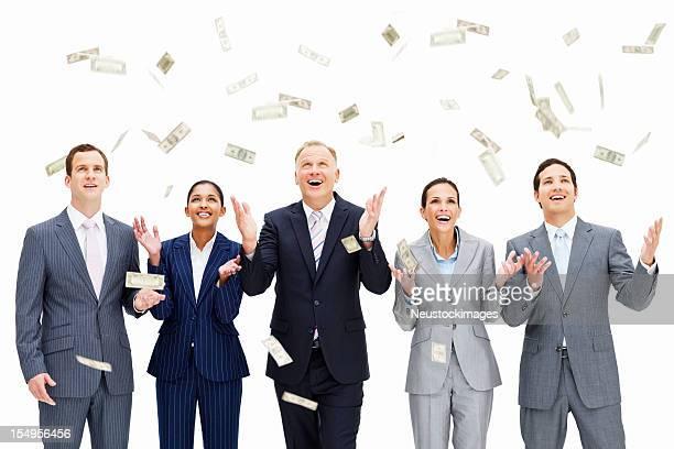 Geld regnet auf lächelnde Geschäftsleute