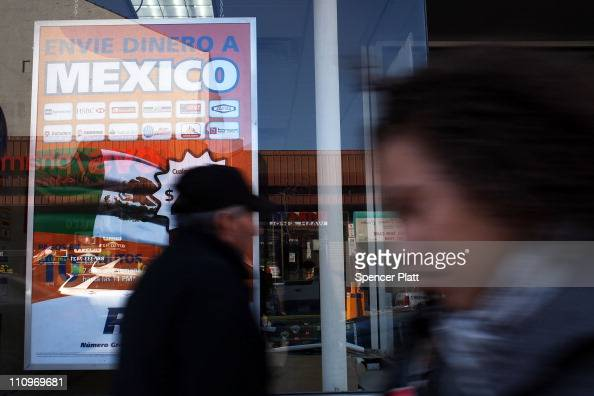 Money transfer advertisements are viewed in the window of a money transfer service specializing in transfers to Latin America on March 28 2011 in...