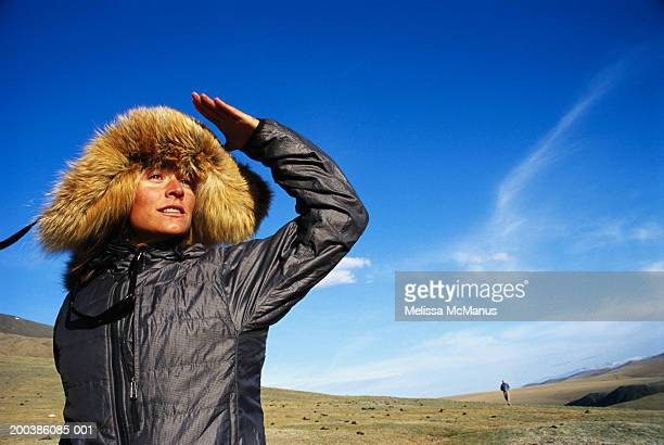Mongolia, female tourist shielding eyes