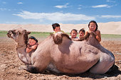 Mongolian children with camel, sand dunes in the background.http://bem.2be.pl/IS/mongolia_380.jpg