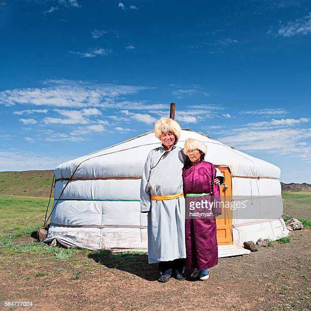 Mongolian couple in national clothing next to ger