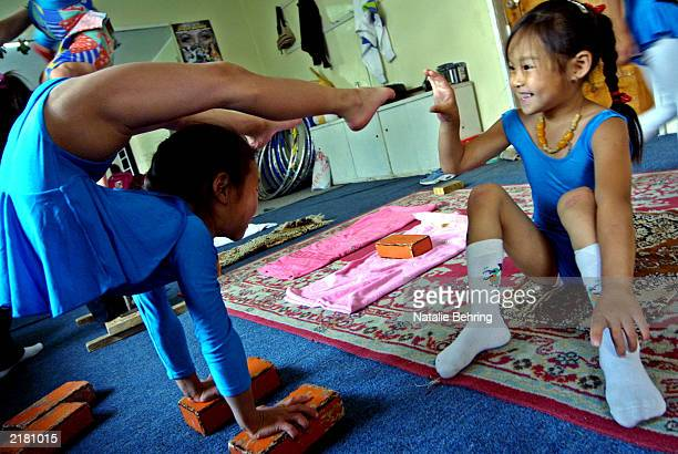 Mongolian girl tickles her friend's foot as she balances during a contortion lesson at the Mongolian State Circus July 17 2003 in Ulan Bator Mongolia...