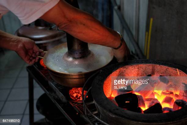 Mongolian hotpot, people using charcoal fire to heat it up