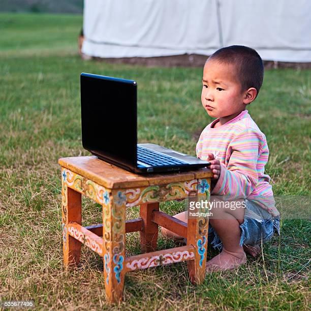 Mongolian little boy using laptop