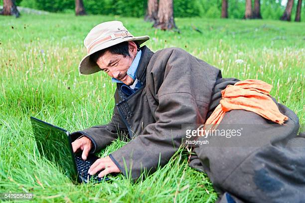 Mongolian man wearing national clothing using laptop