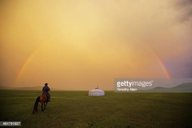 Mongolian Nomad and Ger framed under rainbow