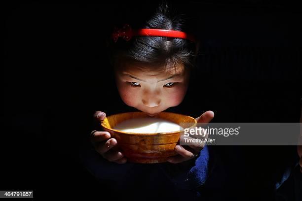 Mongolian nomadic girl drinking bowl of milk