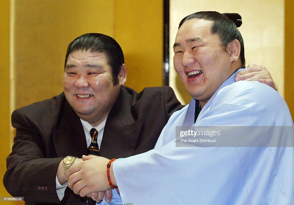 Mongolian ozeki Asashoryu celebrates winning the tournament with his stable master Takasago after day thirteen of the Grand Sumo Kyushu Tournament on...