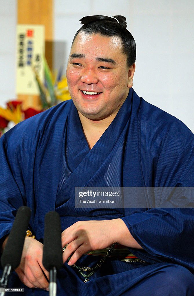 Mongolian Ozeki Harumafuji whose real name is Davaanyamyn Byambadorj smiles during a press conference a day after winning the Grand Sumo Autumn...