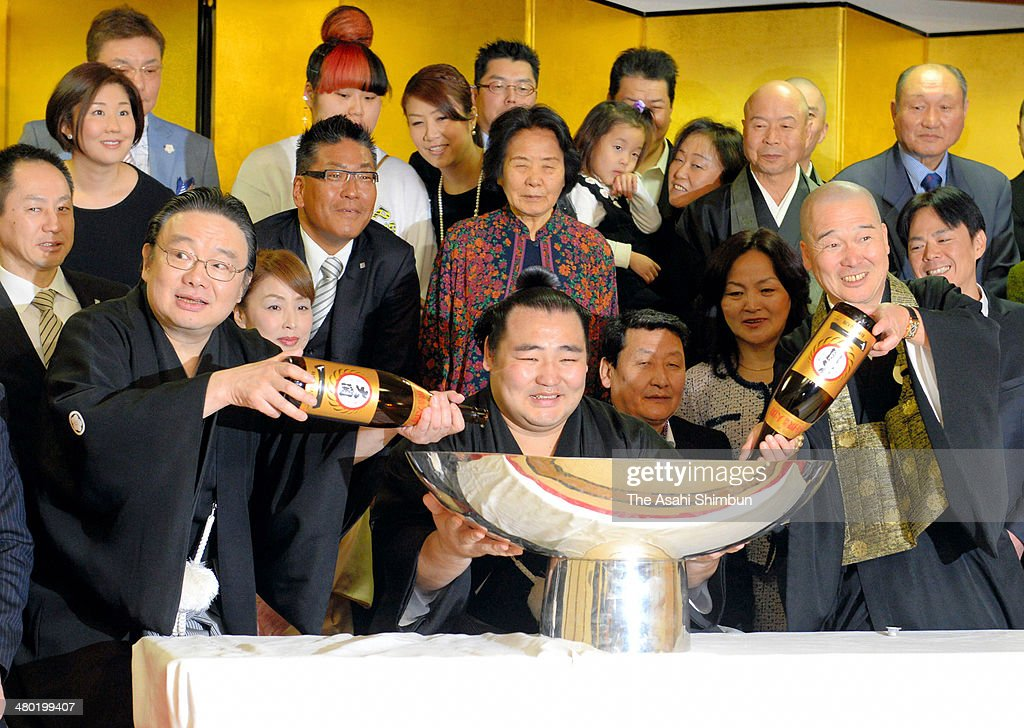 Mongolian ozeki Kakuryu (C), whose real name is Mangaljalavyn Anand is offered Japanese sake to celebrate winning the Grand Sumo Spring Tournament on March 23, 2014 in Osaka, Japan.