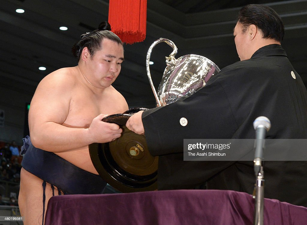 Mongolian ozeki Kakuryu (L), whose real name is Mangaljalavyn Anand receives the trophy after winning the Grand Sumo Spring Tournament at Body Maker Colisseum on March 23, 2014 in Osaka, Japan.