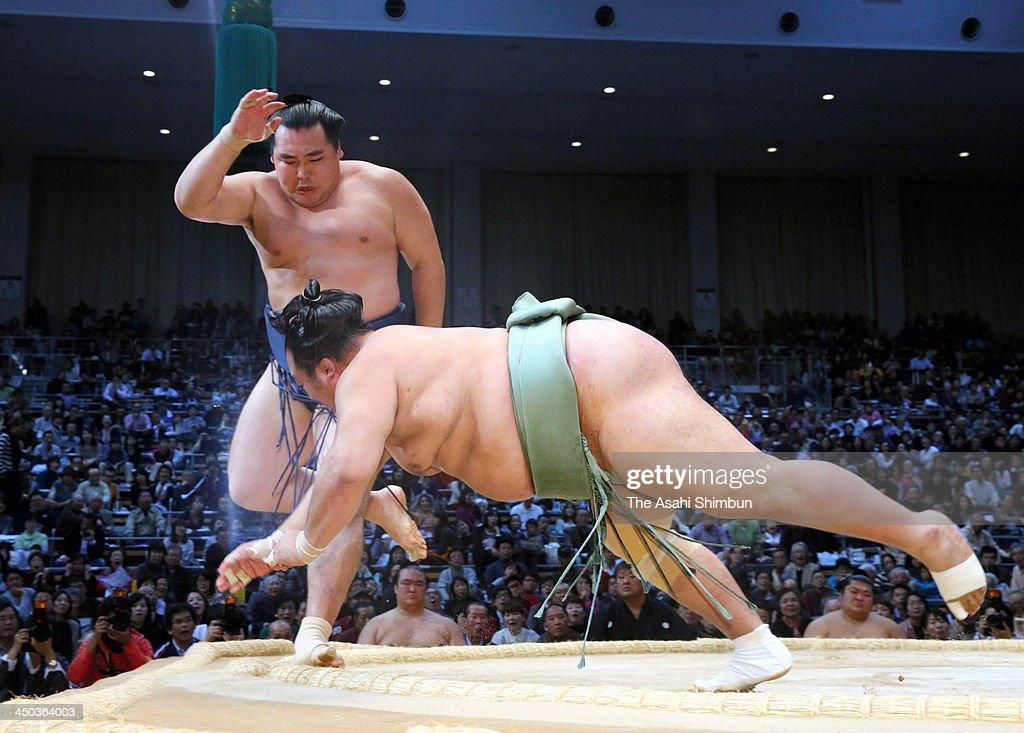 Mongolian ozeki Kakuryu (L) whose real name is Mangaljalavyn Anand throws Toyonoshima to win during day seven of the Grand Sumo Kyushu Tournament at Fukuoka Convention Center on November 16, 2013 in Fukuoka, Japan.