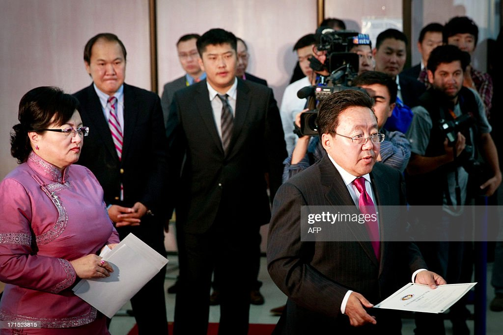 Mongolian President Tsakhia Elbegdorj (Bottom R) votes with his wife Kh. Bolormaa (L) at a polling station during presidential elections in Ulan Bator on June 26, 2013. Mongolians voted on June 26 in a presidential election pitting the front-running incumbent against a champion wrestler and a woman, amid calls for a fairer distribution of the former Soviet satellite's spectacular mining wealth.